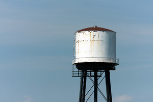 An old rusted water tower isolated over an empty blue sky.