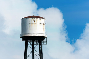 An old rusty water tower over a partially cloudy blue sky.