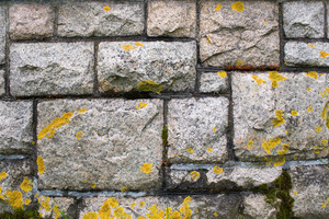 An old stone wall texture that is weathered and covered with some light moss.