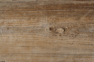 An old wooden texture with grains of sand in the cracks found at the sea shore.