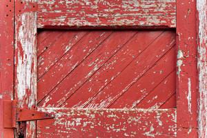 An old worn barn door or wooden fence gate with chipped red paint.