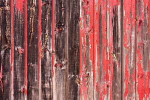 An old worn barn or wooden fence with chipped red paint.