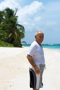 An older Hispanic senior citizen man standing on a tropical beach in the Caribbean.