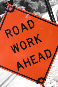 An orange road sign that reads ROAD WORK AHEAD