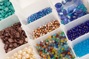 An organizer full of multi colored beads and tools for making jewelry and crafts.