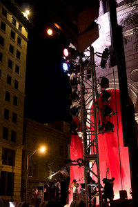 An outdoor musical event with a stage set up in the city streets.