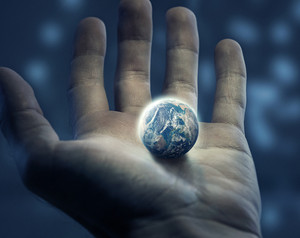 An outstretched hand holds the earth