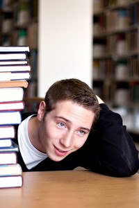 An overwhelmed student with a high pile of textbooks he has to go through to do his homework.