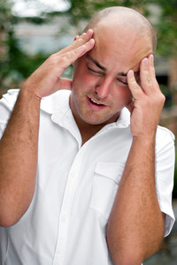 An upset young man grabs his head in annoyance from stress or a headache.