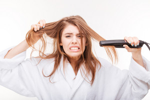 Angry irritated young woman straightening her hair using hair straightener over white background