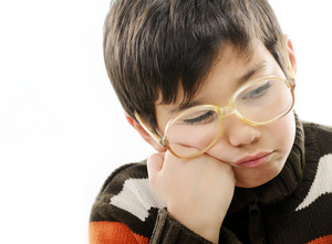 Angry little boy with glasses isolated on white