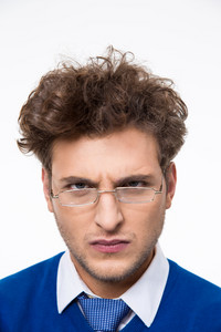 Angry young businessman in glasses looking at camera