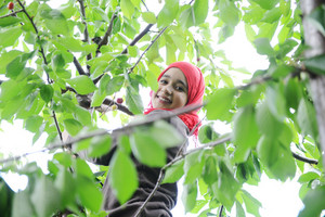 Arabic girl standing on tree arm and smiling
