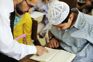 Arabic middle eastern students at school reading Koran