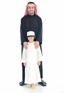 Arabic Muslim father and son standing together