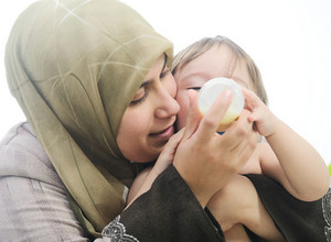 Arabic Muslim mother playing and feeding of her baby