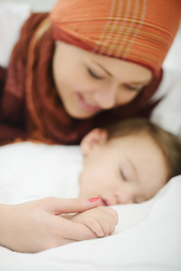Arabic Muslim mother playing and taking care of her baby