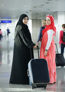 Arabic Muslim teenage girl traveling with her mother, airport transit