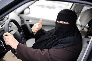 Arabic Muslim woman driving a car and happy for that