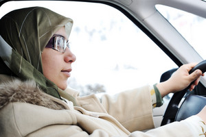Arabic Muslim woman driving car wearing traditional scarf