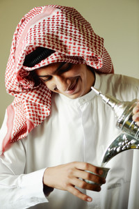 Arabic young man pouring a traditional coffee