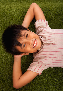 Asian Boy Relaxing On The Lawn