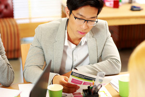 Asian businessman in glasses sitting at the table and reading instruction in office