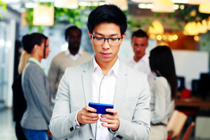 Asian businessman using smartphone in front of colleagues