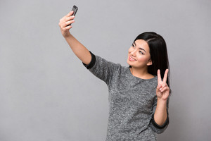Asian girl making selfie using cellphone and showing peace sign