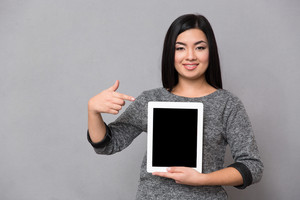 Asian girl staying and pointing on tablet