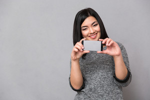 Asian girl taking photos using cellphone
