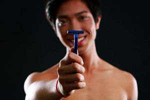 Asian man holding razor. Focus on razor