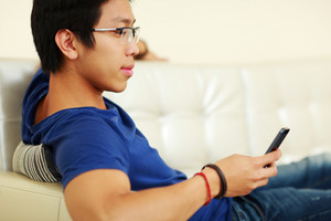 Asian man lying on the sofa and using smartphone at home