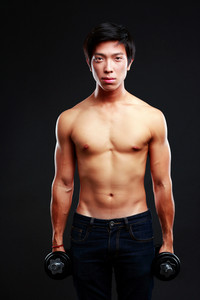 Asian man standing with dumbbells over black background