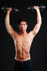 Asian man working out with dumbbell on black background