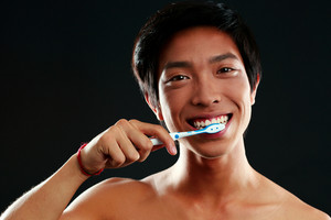 Asian men with toothbrush on black background