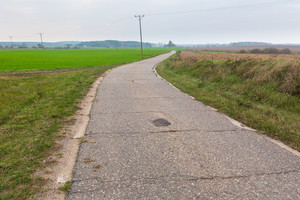 Asphalt rural road in countryside. Polish fields with asphalt road under cloudy sky.