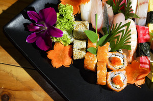 Assorted japanese sushi on a black plate.