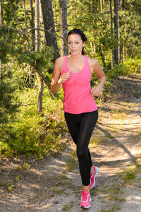 Athlete woman running through forest training in the countryside