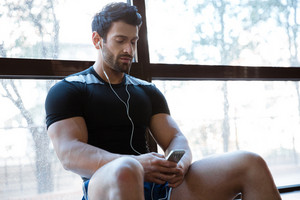 Athleteic man wearing black t-shirt listening to music sitting on windowcill