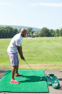 Athletic golfer teeing off at the driving range dressed in casual attire.