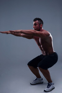 Athletic young muscular man doing squats