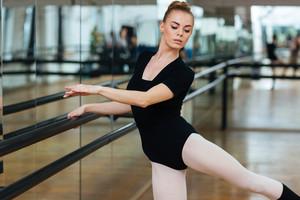 Attractive ballerina practicing in ballet class
