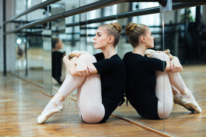Attractive ballerina sitting on the floor in ballet class