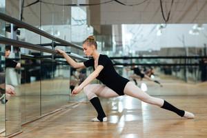 Attractive ballerina warming up in ballet class