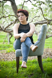 Attractive brunette woman under soft natural lighting near some apple trees. Shallow depth of field.