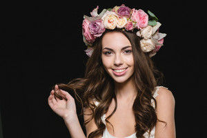 Attractive cheerful young woman with beautiful curly long hair in flower wreath over black background