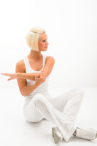 Attractive female fitness instructor stretching arms sitting on white floor