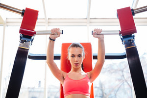 Attractive focused young sportswoman doing exercises in gym