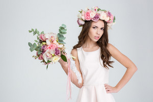 Attractive irritated young woman in white dress and wreath of roses showing bouquet of flowers over white background
